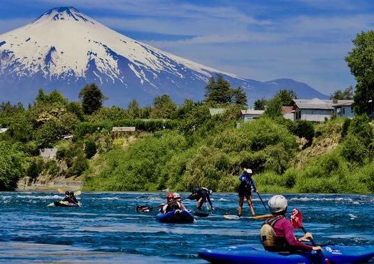 Kayakers learn fundamentals below Volcan Villarrica on the Rio Tolten.
